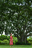 Worthy Tahitian woman stands in front of huge banyan tree in garden, Tahiti, Windward Islands, French Polynesia, South Pacific