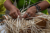 Detail of the hands of a woman weaving a bag from pandanus fiber the traditional way at a cultural festival, Papeete, Tahiti, Windward Islands, French Polynesia, South Pacific