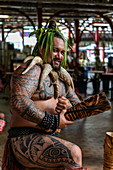 "A Tahitian 'warrior' with tattoos welcomes visitors to the ""Marché Papeete"" market hall, Papeete, Tahiti, Windward Islands, French Polynesia, South Pacific"