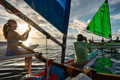 People enjoy sailing out on an outrigger canoe at sunset with a view of Moorea Island, near Papeete, Tahiti, Windward Islands, French Polynesia, South Pacific
