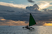 People enjoy cruising on an outrigger canoe with sail at sunset, near Papeete, Tahiti, Windward Islands, French Polynesia, South Pacific