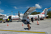 Smiling woman with camera exits Air Tahiti ATR 72-600 airplane on apron at Bora Bora Airport (BOB), Bora Bora, Leeward Islands, French Polynesia, South Pacific