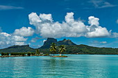Two palm trees and a tiki sculpture on a small island at the entrance to Bora Bora Airport (BOB) harbor with Mount Otemanu in the distance, Bora Bora, Leeward Islands, French Polynesia, South Pacific
