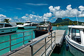 Young man runs along pier at Bora Bora Airport (BOB) with boats and Mount Otemanu in the distance, Bora Bora, Leeward Islands, French Polynesia, South Pacific