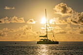Silhouette of catamaran sailboat in Bora Bora Lagoon at sunset, Bora Bora, Leeward Islands, French Polynesia, South Pacific