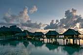 Overwater bungalows of the Sofitel Bora Bora Private Island Resort in the Bora Bora Lagoon at daybreak, Bora Bora, Leeward Islands, French Polynesia, South Pacific