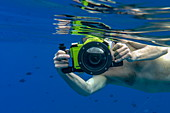 Underwater shot of man with Panasonic Lumix camera with underwater housing while snorkeling in the lagoon of Bora Bora, Bora Bora, Leeward Islands, French Polynesia, South Pacific