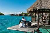 Housekeeper prepares the table for breakfast, which is brought by pirogue outrigger canoe to an overwater bungalow at Sofitel Bora Bora Private Island Resort in Bora Bora Lagoon, Bora Bora, Leeward Islands, French Polynesia, South Pacific