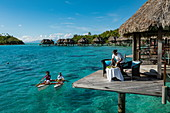 Breakfast is served in a pirogue outrigger canoe to an overwater bungalow at Sofitel Bora Bora Private Island Resort in Bora Bora Lagoon, Bora Bora, Leeward Islands, French Polynesia, South Pacific