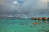 People paddling a canoe in the Moorea Lagoon overlooking the rainbow and overwater bungalows of the Sofitel Ia Ora Beach Resort, Moorea, Windward Islands, French Polynesia, South Pacific