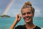 Young blonde woman smiles while tucking a hibiscus flower behind her ear with rainbows over the Moorea Lagoon behind, Moorea, Windward Islands, French Polynesia, South Pacific