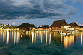 Overwater bungalows of the Sofitel Ia Ora Beach Resort in the Moorea Lagoon at dusk, Moorea, Windward Islands, French Polynesia, South Pacific