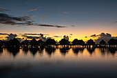 Overwater bungalows of the Sofitel Ia Ora Beach Resort in the Moorea Lagoon at daybreak, Moorea, Windward Islands, French Polynesia, South Pacific
