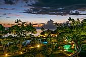 Palm trees and swimming pool at Tahiti Ia Ora Beach Resort (managed by Sofitel) at dusk, near Papeete, Tahiti, Windward Islands, French Polynesia, South Pacific