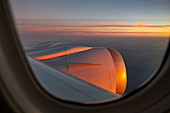 View through window on engine of Air Tahiti Nui Boeing 787 Dreamliner airplane at sunset on the flight from Los Angeles International Airport (LAX) in the USA to Tahiti Faa'a International Airport (PPT) in French Polynesia