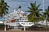Palm trees on the harbor promenade and passenger cargo ship Aranui 5 (Aranui Cruises) on the pier, Papeete, Tahiti, Windward Islands, French Polynesia, South Pacific