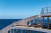People relax on the sundeck of the passenger cargo ship Aranui 5 (Aranui Cruises), at sea between the Tuamotu Islands and the Marquesas Islands, French Polynesia, South Pacific