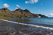 Black sand beach with passenger cargo ship Aranui 5 (Aranui Cruises) on pier in the distance, Taiohae, Nuku Hiva, Marquesas Islands, French Polynesia, South Pacific