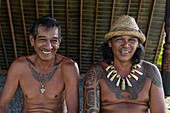 Two men with tattoos - one with a chain made from carved whale bones - smile at the camera in the Te Tumu cultural center, Tekoapa, Ua Huka, Marquesas Islands, French Polynesia, South Pacific