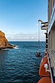 Dinghy is hoisted on board of passenger cargo ship Aranui 5 (Aranui Cruises), Anahehe, Vaipaee Bay, Ua Huka, Marquesas Islands, French Polynesia, South Pacific