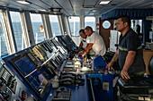 Captain Christophe Dupuy and officers on the bridge of the passenger cargo ship Aranui 5 (Aranui Cruises), Hakahau, Ua Pou, Marquesas Islands, French Polynesia, South Pacific