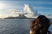 Approach to Bora Bora from the passenger cargo ship Aranui 5 (Aranui Cruises) with a woman's head in the foreground, Bora Bora, Leeward Islands, French Polynesia, South Pacific