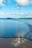 Man on the aft sundeck of the Aranui 5 (Aranui Cruises) passenger cargo ship after passing through the canal into the Bora Bora lagoon, Bora Bora, Leeward Islands, French Polynesia, South Pacific