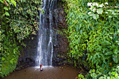 """Aerial view of a beautiful young Tahitian woman dancing in front of a waterfall in """"The Water Gardens of Vaipahi"""", Teva I Uta, Tahiti, Windward Islands, French Polynesia, South Pacific"""
