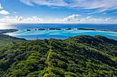 Aerial view of quad ATVs on dirt road through lush mountain vegetation with Motu Islets in the Bora Bora Lagoon in the distance, Bora Bora, Leeward Islands, French Polynesia, South Pacific