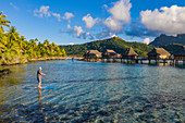 Aerial view of man on SUP stand up paddle board in Bora Bora lagoon with overwater bungalows of Sofitel Bora Bora Private Island Resort behind, Vaitape, Bora Bora, Leeward Islands, French Polynesia, South Pacific