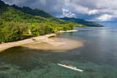 Aerial view of beach and coastline and outrigger racing canoe in Moorea Lagoon, Avamotu, Moorea, Windward Islands, French Polynesia, South Pacific