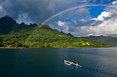 Aerial view of outrigger racing canoe in the Moorea Lagoon with rainbow and mountain backdrop, Avamotu, Moorea, Windward Islands, French Polynesia, South Pacific