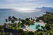 Luftaufnahme des Tahiti Ia Ora Beach Resort (managed by Sofitel) mit Überwasserbungalows und Insel Moorea in der Ferne, nahe Papeete, Tahiti, Windward Islands, Französisch-Polynesien, Südpazifik
