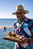 Friendly waiter serves delicious burgers at Malamala Island Beach Club, Mala Mala Island, Mamanuca Group, Fiji Islands, South Pacific