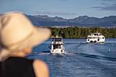 Boats return to Port Denarau Marina in the late afternoon with a woman wearing a sun hat in the foreground, Port Denarau, near Nadi, Viti Levu, Fiji Islands, South Pacific