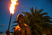 "Friendly Fijian ""warrior"" with torch to light Tiki torches at Pullman Nadi Bay Resort"