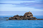 A Fijian stands on a rock and welcomes passengers on the Yasawa Flyer II (South Sea Cruises) catamaran as it approaches the Yasawa Archipelago the traditional way, Kuata Island, Yasawa Group, Fiji Islands, South Pacific
