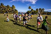 Passagiere von Kreuzfahrtschiff MV Reef Endeavour (Captain Cook Cruises Fiji) spielen Rugby mit einheimischen Jungen auf dem Feld der Dorfschule, Nabukeru, Yasawa Island, Yasawa Group, Fidschi-Inseln, Südpazifik