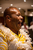 Cruise director Ilisoni Vibosi of cruise ship MV Reef Endeavor (Captain Cook Cruises Fiji) laughs during dinner in the restaurant on board, Sawa-i-Lau Island, Yasawa Group, Fiji Islands, South Pacific