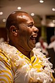 Cruise director Ilisoni Vibosi of cruise ship MV Reef Endeavor (Captain Cook Cruises Fiji) laughs during dinner in the restaurant on board, Sawa-i-Lau Island, Yasawa Group, Fiji Islands, South Pacific