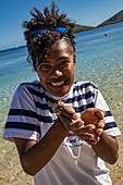 Happy crew member of cruise ship MV Reef Endeavor (Captain Cook Cruises Fiji) holds hermit crab in hands, Yaqeta, Yangetta Island, Yasawa Group, Fiji Islands, South Pacific