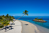 Aerial view of a Residence Villa accommodation in the Six Senses Fiji Resort with coconut trees, beach and family enjoying water sports activities next to a small offshore island, Malolo Island, Mamanuca Group, Fiji Islands, South Pacific