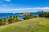 Aerial view of boys playing rugby on the village school field with cruise ship MV Reef Endeavor (Captain Cook Cruises Fiji) in the distance, Nabukeru, Yasawa Island, Yasawa Group, Fiji Islands, South Pacific