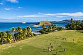 Luftaufnahme von Jungen die Rugby auf dem Feld der Dorfschule spielen mit Kreuzfahrtschiff MV Reef Endeavour (Captain Cook Cruises Fiji) in der Ferne, Nabukeru, Yasawa Island, Yasawa Group, Fidschi-Inseln, Südpazifik