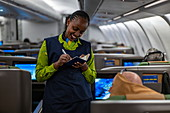 Smiling flight attendant takes a meal order from a passenger in business class on board a RwandAir Airbus A330-300 aircraft on the flight from Brussels International Airport (BRU) in Belgium to Kigali International Airport (KIG) in Rwanda, Africa