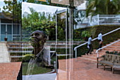 Thoughtful Rwandan man and reflection in window at the Kigali Genocide Memorial Center, Kigali, Kigali Province, Rwanda, Africa