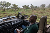 Portrait of a smiling Rwandan man in a safari vehicle operated by luxury resort tented Magashi Camp (Wilderness Safaris), Akagera National Park, Eastern Province, Rwanda, Africa