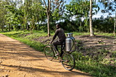 Man transports milk can on bicycle along dirt road, near Kabarondo, Eastern Province, Rwanda, Africa