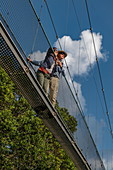 Low angle of view to couple on suspension bridge of Canopy Walkway enjoying the view, Nyungwe Forest National Park, Western Province, Rwanda, Africa