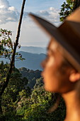 Young woman admires view of trees and mountains, Nyungwe Forest National Park, Western Province, Rwanda, Africa